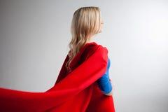 Bohater kobieta patrzeje daleko w odległość przy dobrem Młoda i piękna blondynka w wizerunku superheroine, plecy obrazy stock