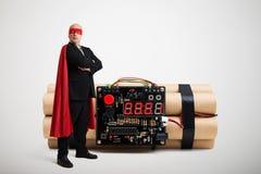 Bohater w czerwonej pelerynie i maskowej trwanie pobliskiej dużej bombie obrazy stock