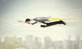 Bohatera biznesowego mężczyzna latanie z strumień paczki rakietą nad cit Zdjęcie Stock