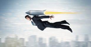 Bohatera biznesowego mężczyzna latanie z strumień paczki rakietą nad cit obraz stock