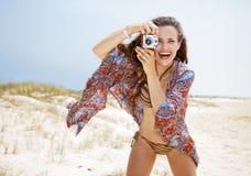 Boheemse vrouw die foto's met retro fotocamera nemen op strand Stock Afbeelding