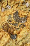 Bohemian chic outfit. Bohemian chic bronze jewelry set on yellow ethnic batik dress. Boho outfit. Top view point Royalty Free Stock Photography
