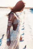 Bohemian chic style. Beautiful girl wearing bohemian chic clothing with flash tattoo on her body posing on the shore in sunlight royalty free stock photos