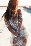 Bohemian chic style. Beautiful girl wearing bohemian chic clothing with flash tattoo on her body posing on the shore in sunlight stock photos