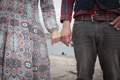 Bohemian couple holding hands by the sea in the summer. Young bohemian couple interlocking fingers and holding hands stood next to each other on a beach in the Royalty Free Stock Images