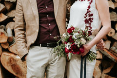 Bohemian couple. Young bohemian couple holding hands and bride holding a beautiful flower bouquet with red peonies and white anemones stock image