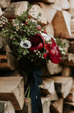 Bohemian flowers bouquet. Beautiful bohemian wedding bouquet with red peonies and white anemones, over wood background stock images