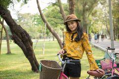 Bohemian girl with bike in summe park. Pretty Asian tan Bohemian woman standing with old bicycle to ride bike in outdoor park. Summer activity for beautiful Stock Photography