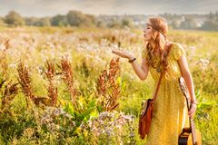 Bohemian girl blowing dandelion seeds in warm sunset light in field