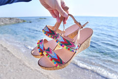 Bohemian greek sandals on the beach. Summer shoes advertisement royalty free stock photo