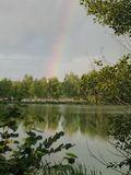 Bohemian pond after the storm with rainbow on a dark cloudy sky Stock Image