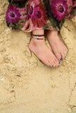 Bohemian style girl`s feet on beach stock images