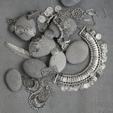 Bohemian style jewelry. Bohemian style silver jewelry set and pebble on vintage grey background. Top view point stock images
