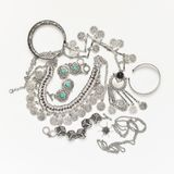 Bohemian style silver jewelry on white. Bohemian style silver jewelry set on white background. Top view point royalty free stock photos