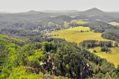 Bohemian Switzerland. Landscape of the Bohemian Switzerland with hills in the distance and rocks in the forest in the foreground Royalty Free Stock Images