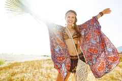 Bohemian chic outdoors with big green tropical leaf rejoicing. Bohemian vibe vacation. cheerful fashion bohemian chic in jeans shorts and cape outdoors in the stock image