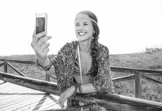 Happy fashion boho girl outdoors with smartphone taking selfie. Bohemian vibe vacation. happy fashion boho girl in cape outdoors in the summer evening with royalty free stock images