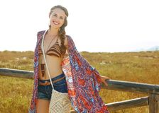 Smiling trendy boho girl outdoors in summer evening near fence Stock Photography