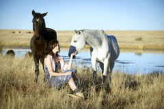 Bohemian woman in field with horses Stock Images