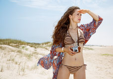 Bohemian woman with retro photo camera on beach looking aside Stock Image