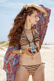 Bohemian woman with retro photo camera on beach looking aside Royalty Free Stock Photography