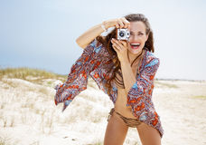 Bohemian woman taking photos with retro photo camera on beach Stock Image