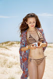 Bohemisk kvinna på den vita stranden som justerar den retro fotokameran Royaltyfria Foton