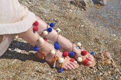 Bohemiska grekiska sandaler med den färgrika pompomannonseringen på stranden royaltyfria bilder