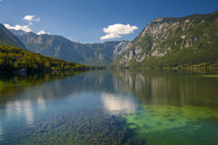Bohinj Lake. With clear water in the foreground and mountains in the background. Clouds reflecting in the water Stock Images