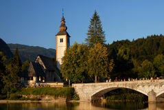 Bohinj lake with a church and bridge infront Stock Images