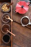 Bohnen des frisch gemahlenen Kaffees in einem Metallfilter und in den Kaffeebohnen mit rotem Kessel Lizenzfreie Stockfotos