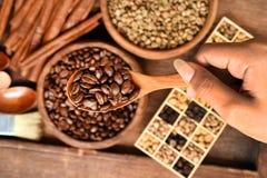 Bohnen des frisch gemahlenen Kaffees in einem Metallfilter und verschiedene Kaffeebohnen in einem quadratischen Kasten Stockfotos