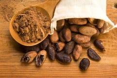 Bohnen des Kakaos (Kakao) auf natürlicher hölzerner Tabelle Lizenzfreies Stockbild