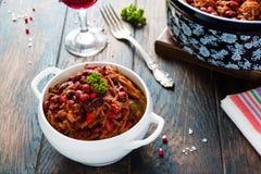 Bohnen mit Schweinefleisch dämpften in der würzigen Tomatensauce mit Zwiebel, Paprika, Bier, Glocke und rosa Pfeffer Lizenzfreies Stockbild