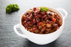 Bohnen mit Schweinefleisch dämpften in der würzigen Tomatensauce mit Zwiebel, Paprika, Bier, Glocke und rosa Pfeffer Stockfoto