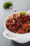 Bohnen mit Schweinefleisch dämpften in der würzigen Tomatensauce mit Zwiebel, Paprika, Bier, Glocke und rosa Pfeffer Lizenzfreies Stockfoto