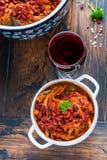 Bohnen mit Schweinefleisch dämpften in der würzigen Tomatensauce mit Zwiebel, Paprika, Bier, Glocke und rosa Pfeffer Stockfotos