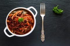 Bohnen mit Schweinefleisch dämpften in der würzigen Tomatensauce mit Zwiebel, Paprika, Bier, Glocke und rosa Pfeffer Stockbilder