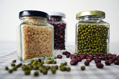 Bohnen u. Körner im quadratischen Glasgefäß Lizenzfreies Stockfoto