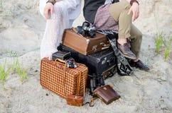 Boho婚礼夫妇坐葡萄酒手提箱,在老减速火箭的照相机和照相机盒附近 免版税库存图片