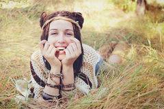 Boho样式微笑的妇女画象,女孩有乐趣说谎室外在秋天晴朗的公园 库存照片