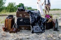 Boho站立近的葡萄酒手提箱的婚礼夫妇,在老减速火箭的照相机、照相机盒和老灯附近 免版税库存图片