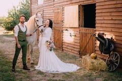 Boho-ähnliche Jungvermählten, die nahe Pferd auf Ranch stehen lizenzfreies stockfoto