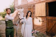Boho-ähnliche Jungvermählten, die nahe Pferd auf Ranch stehen lizenzfreie stockbilder