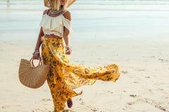 Boho beach clothing style. Girl wearing floral maxi skirt walking barefoot on the sea shore, Thailand, Phuket. Bohemian clothing style Royalty Free Stock Photography