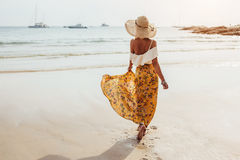 Boho beach clothing style. Girl wearing floral maxi skirt walking barefoot on the sea shore, Thailand, Phuket. Bohemian clothing style Royalty Free Stock Images