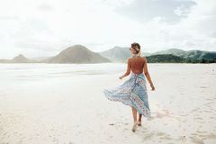 Boho beach style. Woman wearing ethnic flying dress walking barefoot at the beach, Lombok, Indonesia Royalty Free Stock Photo