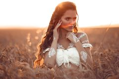 Boho chic style. Portrait of bohemian girl with white art posing over wheat field enjoying at sunset. Outdoors photo. Tranquility stock photography