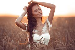 Boho chic style. Portrait of bohemian girl with white art posing over wheat field enjoying at sunset. Outdoors photo. Tranquility royalty free stock images