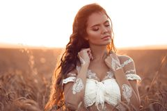 Boho chic style. Portrait of bohemian girl with white art posing over wheat field enjoying at sunset. Outdoors photo. Tranquility royalty free stock photos